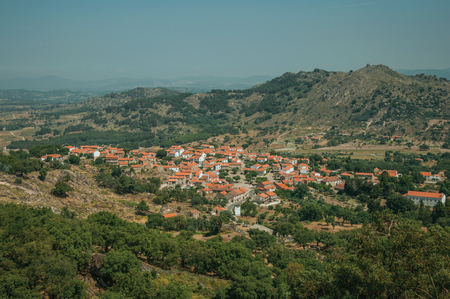 Village with roofs on white houses in hilly landscape covered by rocks and olive tree fields, in a sunny day near Monsanto. Considered one of the cutest and most peculiar historic village of Portugal. 写真素材
