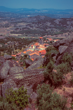 Hilly landscape covered by trees and rocks with roofs of the Monsanto village underneath. This township is considered one of the cutest and most peculiar historic village of Portugal. Vintage filter. 写真素材