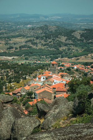 Hilly landscape covered by trees and rocks in a sunny day, with roofs of the Monsanto village underneath. This township is considered one of the cutest and most peculiar historic village of Portugal.