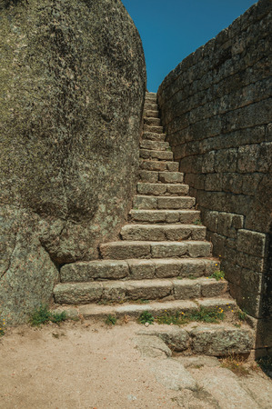 Stone narrow staircase between wall and big rock, in a sunny day at the Castle of Monsanto. Considered one of the cutest and most peculiar historic village of Portugal