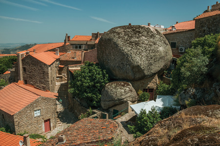 Monsanto, Portugal - July 13, 2018. Rooftops of old stone houses with rocks and alley among them in a sunny day at Monsanto. Considered one of the cutest and most peculiar historic village of Portugal