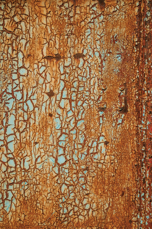 Close-up of rusted metal plate covered by cracks and peeling paint, forming a singular background at Monsanto. Considered one of the cutest and most peculiar historic village of Portugal.