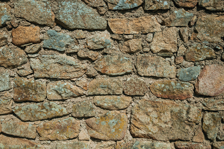 Close-up of wall made of rough stones with moss and lichens, forming a singular background in a sunny day at Monsanto. Considered one of the cutest and most peculiar historic village of Portugal.