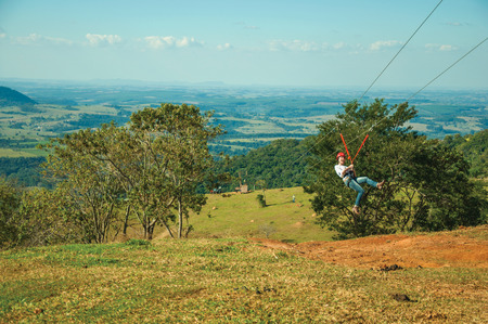 Pardinho, Brazil - Woman descending by cables in a sport called zip-line over meadows and trees in a valley near Pardinho. A small rural village in the countryside of Sao Paulo State.