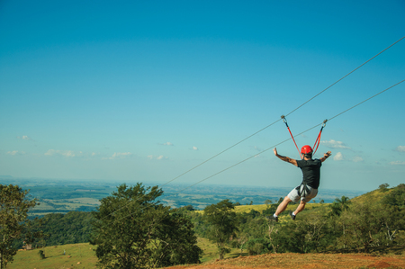 Pardinho, Brazil - Man descending by cables in a sport called zip-line over meadows and trees in a valley near Pardinho. A small rural village in the countryside of Sao Paulo State. Stock Photo