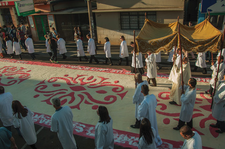 Sao Manuel, Brazil - May 31, 2018. Religious procession passing by a colorful sand carpet at the celebration of Holy Week on a street of Sao Manuel. A little town in the countryside of Sao Paulo State