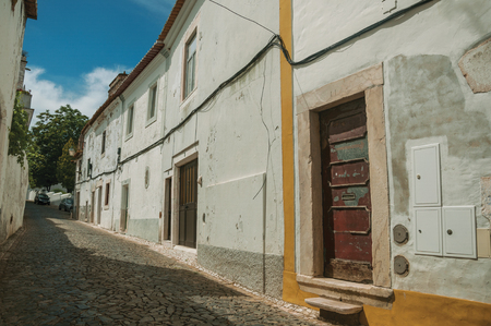 Old houses with doors on alley with cobblestone pavement in sunny day at Estremoz. A nice little historic town with several buildings made of marble on eastern Portugal. Stock Photo
