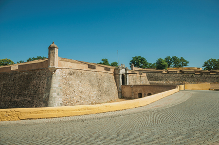 Deserted street at the city wall with an entrance door and small bridge over the dry moat, in a sunny day at Elvas. A gracious star-shaped fortress city on the easternmost frontier of Portugal.