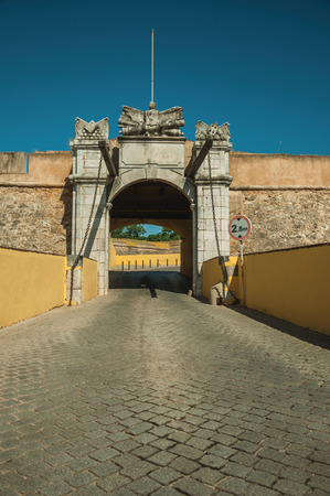 Deserted street going toward the richly decorated city wall gateway and traffic sign, in a sunny day at Elvas. A gracious star-shaped fortress city on the easternmost frontier of Portugal. Stock Photo