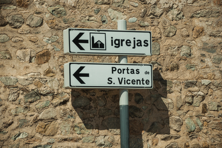 Street signpost in front of a stone wall in a sunny day, indicating public services and city attractions at Elvas. A gracious star-shaped fortress city on the easternmost frontier of Portugal. 스톡 콘텐츠