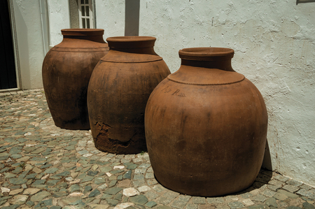 Campo Maior, Portugal - Large earthenware vessels over floor and rough plaster wall at Campo Maior. A cute little town with Roman, Moorish and medieval influences in eastern Portugal. Banco de Imagens