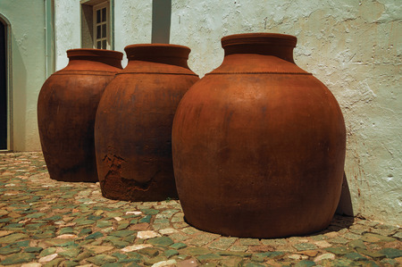 Close-up of large earthenware vessels over deserted floor and rough plaster wall at Campo Maior. A cute little town with Roman, Moorish and medieval influences in eastern Portugal. Retouched photo. Banco de Imagens