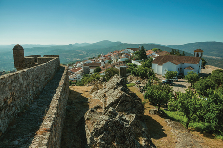 Old houses and church on top of ridge with stone wall and mountainous landscape, as seen from the Castle of Marvao. An amazing medieval fortified village perched on a granite crag in eastern Portugal.