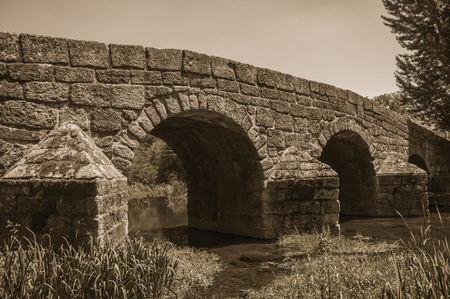Old Roman stone bridge still in use over the Sever River with plants on the bank at Portagem. A district of Marvão at the bottom of a lush wooded valley in eastern Portugal. Black and white photo. Stok Fotoğraf