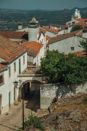 Charming old houses with whitewashed wall in cobblestone alley and passageway under arch, in a sunny day at Marvao. An amazing medieval fortified village perched on a granite crag in eastern Portugal. Reklamní fotografie