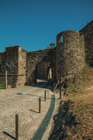 Arched gateway in the outer wall made of rough stone with pathway and watchtower, in a sunny day at Marvao. An amazing medieval fortified village perched on a granite crag in eastern Portugal.