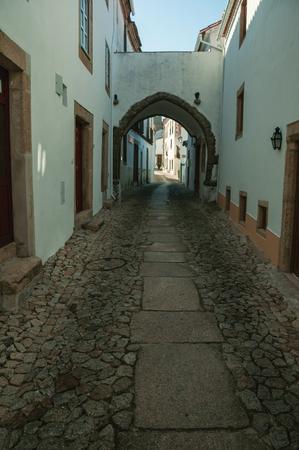 Charmante alte Häuser mit weiß getünchten Wänden in Kopfsteinpflastergasse und Durchgang unter Bogen, an einem sonnigen Tag in Marvao. Ein erstaunliches mittelalterliches befestigtes Dorf, das auf einem Granitfelsen im Osten Portugals thront. Standard-Bild