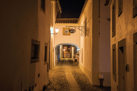 Marvao, Portugal - Charming old houses on cobblestone alley and passageway under arch at dusk in Marvao. An amazing medieval fortified village on a granite crag in eastern Portugal.