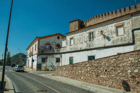 Street with stone wall and old white houses with worn plaster wall, in a sunny day at Portalegre. A nice little town at the bottom of Mamede Mountain Range in eastern Portugal.