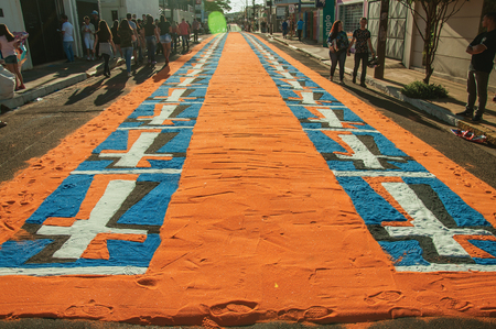 Sao Manuel, Brazil - May 31, 2018. People walking on street and admiring colorful sand carpets made for the celebration of Holy Week of Sao Manuel. A little town in the countryside of Sao Paulo State. Editorial