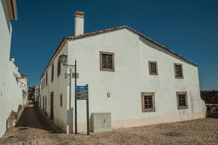 Facade of old whitewashed wall house in front a cobblestone square and narrow ally, in sunny day at Marvao. An amazing medieval fortified village perched on a granite crag in eastern Portugal.