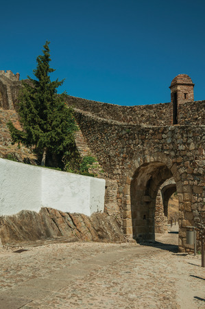 Arched gateway in the city outer wall made of stone with pathway under it and watchtower, on sunny day at Marvao. An amazing medieval fortified village perched on a granite crag in eastern Portugal. Banco de Imagens