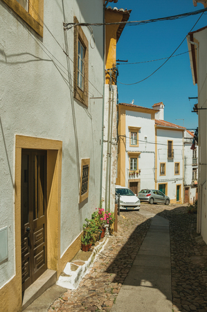 Facade of old colorful houses with whitewashed wall in alley with cars, in a sunny day at Castelo de Vide. Nice little town with medieval castle to ensure the defense of the Portugal eastern border.