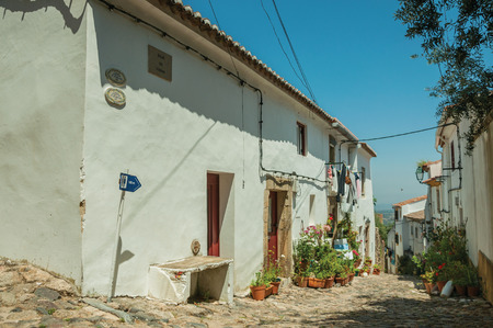 Castelo de Vide, Portugal, July 10, 2018. Old houses with flowered pots in front of alley at Castelo de Vide. Nice little town with medieval castle to ensure the defense of the Portugal eastern borde,