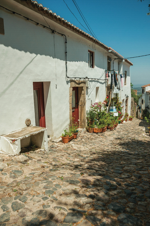 Lovely facade of old whitewashed houses and flowered pots in front of cobblestone alley at Castelo de Vide. Nice little town with medieval castle to ensure the defense of the Portugal eastern border. Reklamní fotografie