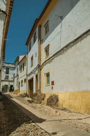 Lovely facade of old colorful houses with whitewashed wall in cobblestone alley on slope at Castelo de Vide. Nice little town with medieval castle to ensure the defense of the Portugal eastern border.