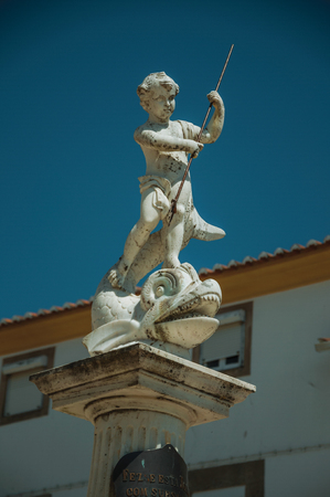 Curious marble statue on top of pillar in sunny day at Castelo de Vide. Nice little town with medieval castle to ensure the defense of the Portugal eastern border.