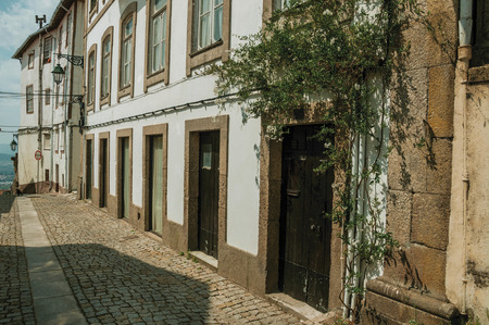 Charming facade of old mansion with stone decoration and flowered shrubs in deserted alley at Covilha. Known as the town of wool and snow, stands at Estrela ridge proximity in eastern Portugal.