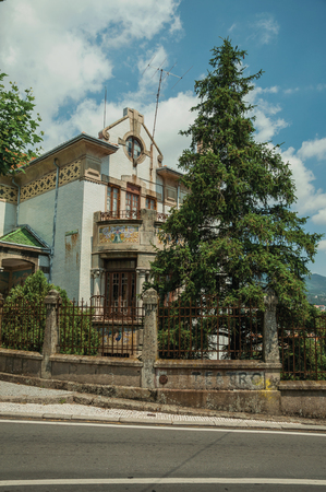 Old charming mansion with facade decorated by ceramics tile and leafy trees, in a sunny day at Covilha. Known as the town of wool and snow, stands at Estrela ridge proximity in eastern Portugal.