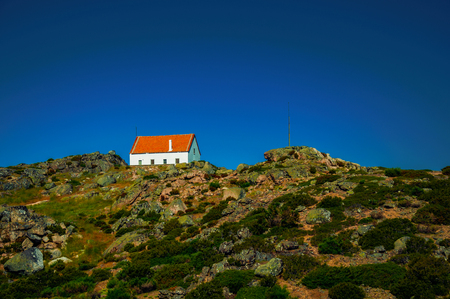 House on top of hilly landscape covered by bushes and rocks on highlands at the Serra da Estrela. The highest mountain range in continental Portugal, with astonishing scenery. Retouched photo.