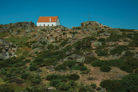 Lonely house on top of hilly landscape covered by bushes and rocks on highlands, in a sunny day at the Serra da Estrela. The highest mountain range in continental Portugal, with astonishing scenery.