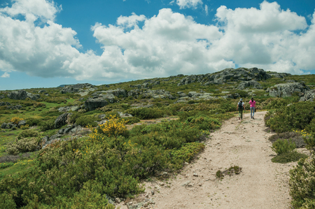 Serra da Estrela, Portugal - July 12, 2018. Woman and girl walking along a trail on highlands at the Serra da Estrela. The highest mountain range in continental Portugal, with astonishing scenery.