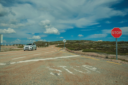 Car passing through road with STOP traffic sign on rocky landscape and bush fields, at the highlands of Serra da Estrela. The highest mountain range in continental Portugal, with astonishing scenery. Редакционное