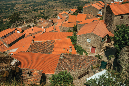 Rooftops of old stone houses with rounded rocks and narrow alley amid them, on hilly landscape in a sunny day at Monsanto. Considered one of the cutest and most peculiar historic village of Portugal.