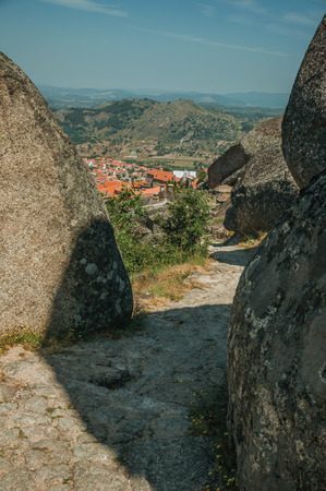 Pathway passing through big round rocks and the Monsanto village underneath the hilly landscape. This township is considered one of the cutest and most peculiar historic village of Portugal.