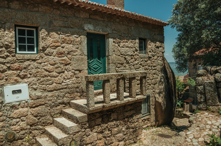 Charming facade of old house with stone staircase going to a small porch on deserted alley, in a sunny day at Monsanto. Considered one of the cutest and most peculiar historic village of Portugal.