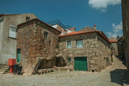 Charming facade of old stone houses with wooden door in deserted alley on slope, on a sunny day at Monsanto. Considered one of the cutest and most peculiar historic village of Portugal.