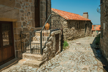 Facade of old house and stone staircase with iron railing on cobblestone alley at Linhares da Beira. A medieval hamlet with unique architectural diversity fruit of several times, in eastern Portugal. Banco de Imagens
