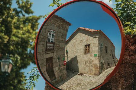 Charming facade of old houses on cobblestone square, reflected in street mirror at Linhares da Beira. A medieval hamlet with unique architectural diversity fruit of several times, in eastern Portugal. Banco de Imagens