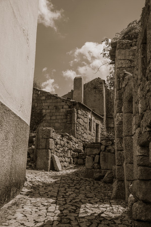 Narrow cobblestone alley and rustic stone old houses at Linhares da Beira. A medieval hamlet with unique architectural diversity fruit of several times, in eastern Portugal. Black and white photo. Banco de Imagens