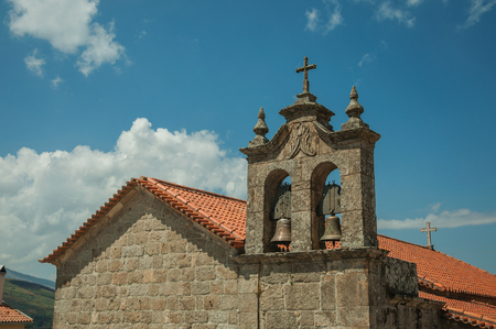 Stone church roof and campanile with bronze bells, in a sunny day at Linhares da Beira. A medieval hamlet with unique architectural diversity fruit of several times, in eastern Portugal. Banco de Imagens