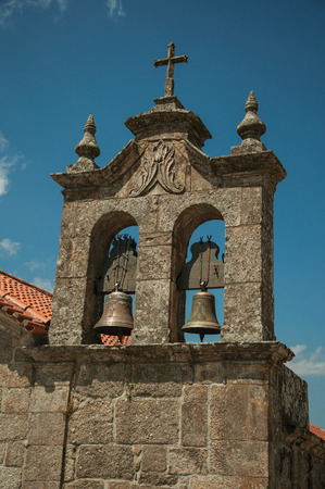 Stone campanile in baroque style with bronze bells from church, in a sunny day at Linhares da Beira. A medieval hamlet with unique architectural diversity fruit of several times, in eastern Portugal. Banco de Imagens