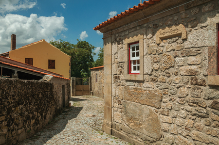 Facade of old house with stone wall and small window in a cobblestone alley at Linhares da Beira. A medieval hamlet with unique architectural diversity fruit of several times, in eastern Portugal.