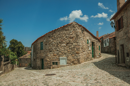 Corner of old stone house between two cobblestone alleys, in a sunny day at Linhares da Beira. A medieval hamlet with unique architectural diversity fruit of several times, in eastern Portugal.