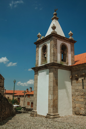 Bell tower from church in baroque style with exquisite stone decoration at Linhares da Beira. A medieval hamlet with unique architectural diversity fruit of several times, in eastern Portugal. Banco de Imagens - 124404153
