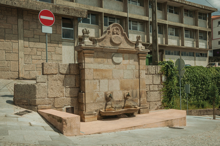 A public fountain made of stone in an empty sidewalk and NO ENTRY road signpost, in a sunny day at Gouveia. A nice country town with gardens and captivating historical heritage, in eastern Portugal.